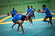 A raider is seen kicking the defendant team-member while he tries to catch him during the kabbadi training sessions as part of the training at a month long camp for the Indian national Kabbadi team in Sport Authority of India Sports Complex in Bisankhedi, outskirts of Bhopal, Madhya Pradesh, India.
