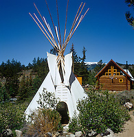 A Sioux-style tepee stands amidst various other wooden structures on the settlement