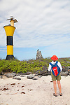 A tourist looks at a Galapagos Hawk on the Southeastern Island of Espanola in the Galapgos National Park, in Ecuador, South America which is home to sea lions, marine iguanas, blue footed boobies, and Nazca Boobies plus many different species of animals and birds.