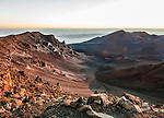 A look into the crater of Mt. Haleakala, as lit by the rising sun at dawn, from its rim (elev. 10,000 ft). Mt. Haleakala is a dormant volcano that forms the majority of the land area of Maui.