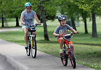 NWA Democrat-Gazette/DAVID GOTTSCHALK  Michelle Parker follows her son Eli, 5, Tuesday, April, 18, 2017, up the sidewalk on Block Avenue along Walker Park in Fayetteville. The two were exploring the Razorback Regional Greenway Trail and completing a seven mile ride. Walker Park was the second park added to the city parks system in 1949.