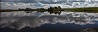 Clouds float in sky and drift in the water - reflected in Bethany Reservoir near Livermore, California.