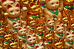 The Maneki Neko literally &quot;Beckoning Cat&quot; is also known as Welcoming Cat, Lucky Cat, Money cat or Fortune Cat.  They are common Japanese decorations, made of porcelain or ceramic,  which is believed to bring good luck to the owner. The sculpture depicts a cat usually  a Japanese Bobtail beckoning with an upright paw, and is usually displayed at the entrance of shops, restaurants  and other businesses. Some of the sculptures are electric and have a slow moving paw beckoning. In the design of the sculptures, a raised right paw supposedly attracts money, while a raised left paw attracts customers.