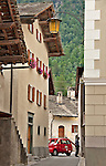 Houses, a narrow street, a red car, and a view of the mountains in the small town of Viscoprano in the Swiss valley of Bregaglia