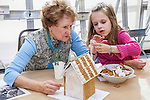 Grandmother helps her granddaughter decorate a ginger bread house
