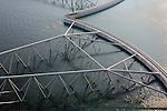 Nederland, Zuid-Holland, Nieuwe Waterweg, 19-09-2009; Functioneringssluiting Maeslantkering: de waterkering in de Nieuwe Waterweg wordt een maal per jaar, voordat het stormseizoen begint, getest. Tijdens  het sluiten van de kering ligt alle scheepvaartverkeer naar de Rotterdamse haven stil. De eigenlijk kering bestaat uit twee (holle) kerende wanden die nadat ze op hun plaats zijn gebracht, afgezonken worden door er water in te pompen..De Maeslantkering sluit normaal gesproken alleen bij dreigende stromvloed en bij een waterstand van 3 meter of meer boven NAP. De kering, onderdeel van de Deltawerken, vormt samen met de Hartelkering de Europoortkering en beschermt Rotterdam en achterland bij extreme waterstanden. .Netherlands, Hoek van Holland - Rotterdam harbour. Aerial view of the new storm surge barrier (Maeslantkering) in the Nieuwe waterweg during the so-called functioning closure, taking place one a year before the storm season begins. The waterway, leading to the Port of Rotterdam (at the horizon), is closed during the test..luchtfoto (toeslag), aerial photo (additional fee required).foto/photo Siebe Swart