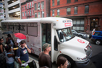 Shoppers wait for a free shuttle bus outside the new Target store in the East Harlem neighborhood of New York on its opening day, Sunday, July 25, 2010. Target, which is the second largest discount retailer in the United States has opened its first permanent Manhattan location in the East River Plaza, a vertical mall. The company has projected revenue of $90 million in the stores first year of operation (© Richard B. Levine).