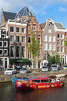 Tourists on canal boat sightseeing cruise trip pass Johannes Restaurant on canalside street in Herengracht, Amsterdam, Holland