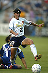 Allie Sullivan (22) pushes past a fallen Danielle Slaton at SAS Stadium in Cary, North Carolina on 7/19/03 during a game between the Carolina Courage and San Diego Spirit. Carolina won the game 1-0