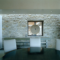 In the dining room of a contemporary adobe house in New Mexico the massive stone walls have been constructed from stone quarried in Telluride, Colorado