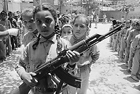1970, Beirut, Lebanon --- Young girl holding a machine gun, with other children in training as commandos, at a Palestinian refugee camp which gave strong support to Al Fatah, the pre-PLO (Palestine Liberation Organization) group of which Yassir Arafat was the leader. --- Image by &copy; Owen Franken/CORBIS