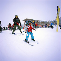 A Young Child learning to Downhill Ski with Father holding Harness, on Whistler Mountain, Whistler Resort, British Columbia, Canada