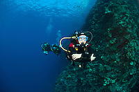 Divers on a drift dive at the backwall Molokini Maui Hawaii.Over 150 feet visibility.