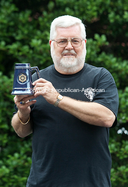 WATERBURY, CT.-26 JUNE 2013 062713DA02-  Jack Shea holds a mug that represents 100,000 sunfish sail boat produced by AMF Alcort/Paceship Inc., a sailboat manufacturer that was once on South Leonard Street in Waterbury, Shea along with other employees of the company will attend their 4th reunion next month. <br /> Darlene Douty Republican-American