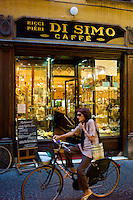 Cyclist passing Di Simo Caffe, Ricci and Pieri, in Via Fillungo,  Lucca, Italy