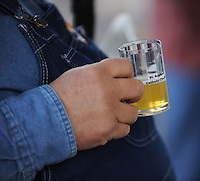 NWA Democrat-Gazette/ANDY SHUPE<br /> A participant holds a tasting mug Saturday, Oct. 17, 2015, during the second St. Raphael Catholic Church Brewtober Chilifest in Springdale. The event gave attendees the chance to taste home-brewed beers and ciders and sample chili with awards going to the two winners as determined by a popular vote.