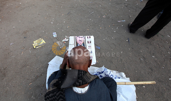 An Egyptian man  read Egyptian newspapers in Cairo's landmark Tahrir Square on June 3, 2012 after a night of protests. Hundreds of demonstrators are occupying Tahrir Square after a court sentenced ousted president Hosni Mubarak and his interior minister Habib al-Adly to life in prison but acquitted six security chiefs in the deaths of protesters last year. Photo by Majdi Fathi