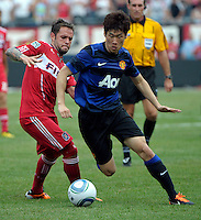 Manchester United midfielder Ji-Sung Park (13) dribbles around Chicago Fire midfielder Daniel Paladini (11).  Manchester United defeated the Chicago Fire 3-1 at Soldier Field in Chicago, IL on July 23, 2011.