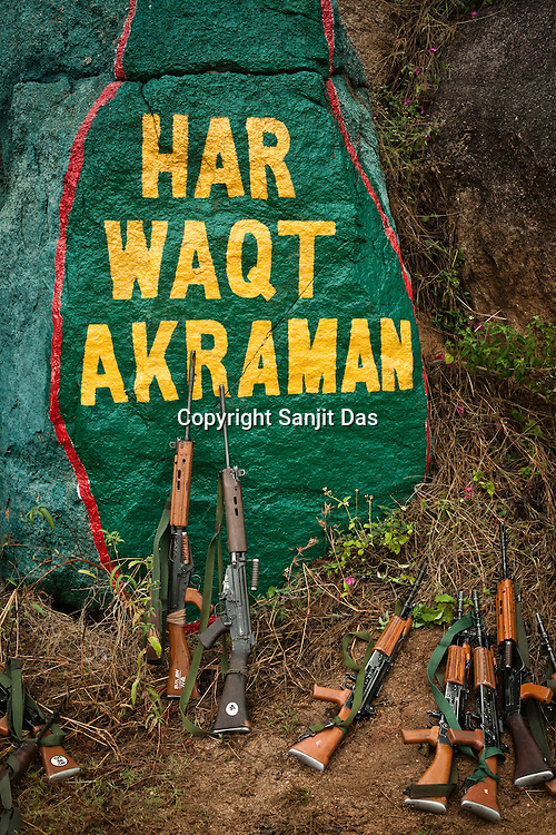 Weapons lie on the ground (in front of the sign on rock - Attack, always) while commandoes train at the Central Jungle Warfare College in Kanker, Chhattisgarh, India. Photograph by Sanjit Das/Panos for The Times.
