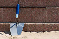 a trowel is resting against stone wall on a beach