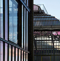 Plant History Glasshouse, formerly the Australian Glasshouse, 1830s, Charles Rohault de Fleury, Jardin des Plantes, Museum National d'Histoire Naturelle, Paris, France, (foreground) and the New Caledonia Glasshouse, formerly The Mexican Hothouse (background), 1830s, Charles Rohault de Fleury.  Low angle view in the late afternoon light, showing the glass and metal structures. The New Caledonia Glasshouse, or Hothouse, was the first French glass and iron building.