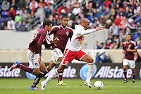 Thierry Henry (14) of the New York Red Bulls is chased by a pair of Colorado Rapids defenders. The New York Red Bulls defeated the Colorado Rapids 4-1 during a Major League Soccer (MLS) match at Red Bull Arena in Harrison, NJ, on March 25, 2012.