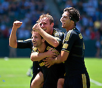 CARSON, CA – July 24, 2011: Mike Magee (18), Chris Birchall (8) and Omar Gonzalez (4) of LA Galaxy celebrate Magee's goal during the match between LA Galaxy and Manchester City FC at the Home Depot Center in Carson, California. Final score Manchester City FC 1 and LA Galaxy 1. Manchester City wins shoot out 7, LA Galaxy 6.