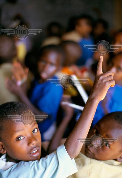Children raise their hands at an orphanage school.