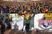 """As the 1996-97 NFC Championship between the Green Bay Packers and the Carolina Panthers commences, Paul Hornung makes short work of someone's banner in his mock attempt at a Lambeau Leap on January 12, 1997. This was the first title game in Green Bay since the """"Ice Bowl"""" in 1967."""