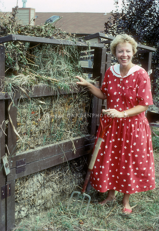 Smiling woman in red dress standing next to wooden and wire compost bin, with garden pitchfork near house