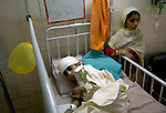 In the Sheikh Zayad Hospital in Lahore, Pakistan, 12-year old Arshad, who received a serious head injury in the October 8, 2005, earthquake, is watched over by his sister. They are from the nearly destroyed village of Slangari, near Balakot.