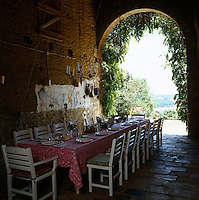 A French summer dining room in a former cowshed features a long table laid for lunch and painted country chairs