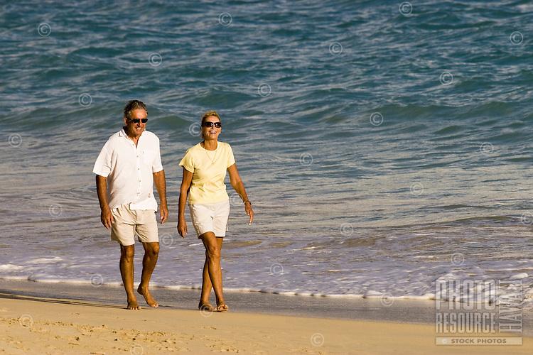 A retired couple walks Kailua beach enjoying the warm light of another windward Oahu sunrise