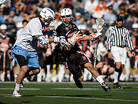 John Greeley (9) of Johns Hopkins applys a check to Mike Grossman (8) of Princeton during the Face-Off Classic in at M&T Stadium in Baltimore, MD