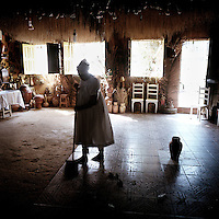 A woman sweeps the floor of a Candomble Terreiro (Temple) after the worshippers have all left.
