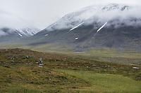 Female hiker hiking through mountain landscape near Sälka hut, Kungsleden trail, Lapland, Sweden