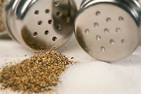 Salt and Pepper Shaker with spilled pepper and salt in front of them