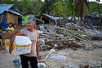 A woman is pleased with the relief goods. The spirit of the Philippine islanders remains strong even though they lost most of their possessions.