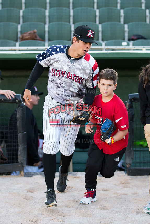 Kannapolis Intimidators second baseman Mitch Roman (10) takes the field with a young fan prior to the game against the Lakewood BlueClaws at Kannapolis Intimidators Stadium on April 7, 2017 in Kannapolis, North Carolina.  The BlueClaws defeated the Intimidators 6-4.  (Brian Westerholt/Four Seam Images)