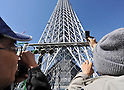 March 18, 2011, Tokyo, Japan - Spectators take pictures of the Tokyo Sky Tree under construction in downtown Tokyo as the  telecommunication tower reaches the 634-meter tidemark on Friday, March 18, 2011. The new Tokyo landmark, the world's tallest self-standing structure with two observatories and commercial facilities, is scheduled to begin operating in spring of 2012. (Photo by Natsuki Sakai/AFLO) [3615] -mis-
