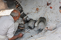 Bhaktapur, Nepal.  Potter at Work Tending his Kiln in Potters' Square.