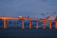 Trucks transport goods over a bridge as the sun sets.  Lofoten is where the World's largest and last cod stocks are found, in the Barent's Sea. Fishing is as strong an industry as tourism in this region.