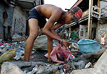 In a Manila neighborhood at the edge of a huge municipal dump, children work recycling items they rescued from the dump...