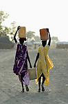 Women carry home water in Agok, a town in the contested Abyei region where tens of thousands of people fled in 2011 after an attack by soldiers and militias from the northern Republic of Sudan on most parts of Abyei. Although the 2005 Comprehensive Peace Agreement called for residents of Abyei--which sits on the border between Sudan and South Sudan--to hold a referendum on whether they wanted to align with the north or the newly independent South Sudan, the government in Khartoum and northern-backed Misseriya nomads, excluded from voting as they only live part of the year in Abyei, blocked the vote and attacked the majority Dinka Ngok population. The African Union has proposed a new peace plan, including a referendum to be held in October 2013, but it has been rejected by the Misseriya and Khartoum. The Catholic parish of Abyei, with support from Caritas South Sudan and other international church partners, has maintained its pastoral presence among the displaced and assisted them with food, shelter, and other relief supplies.