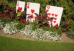 Flower garden with large playing cards display.