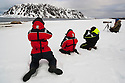 Norway, Svalbard, tourists sitting in snow photographing walruses