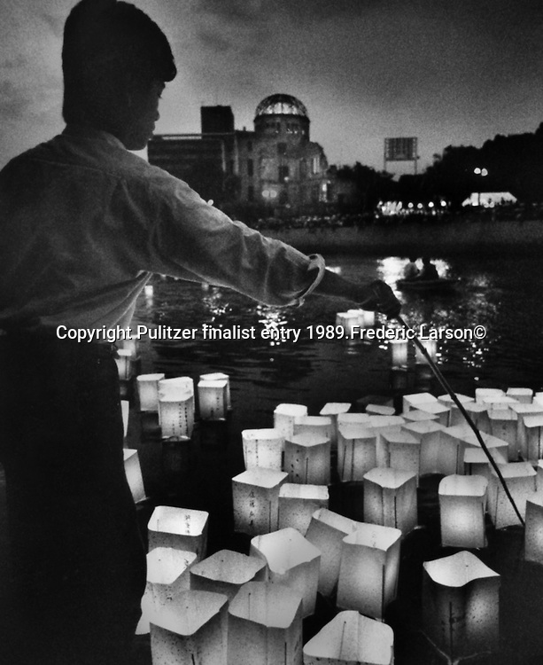 """Colorful paper lanterns that are symbolic of the victims"""" souls are set adrift on one of Hiroshima's seven rivers during the anniversary of the bombing.  In the background, the A-bomb Dome is visible, the only original building still standing at the hypocenter. .Pulitzer finalist entry 1989 Frederic Larson©"""