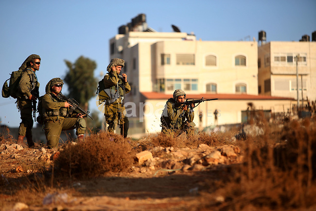 Israeli soldiers take position during clashes with Palestinian protesters nearby the Jalazoun refugee camp and the Jewish settlement of Beit El, north of Ramallah, after a demonstration in reaction to the death of a Palestinian toddler who was burned in an arson attack by suspected Jewish settlers on two homes in the occupied West Bank on July 31, 2015. Photo by Shadi Hatem