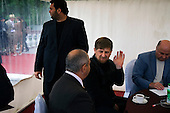 """Chechen President Ramzan Kadyrov talks attends a horse race in Moscow's Hippodrome. While he talks to another guest, his bodyguard looks out of the VIP tent. .Kadyrov's horse, """"Royal Quiet"""", came first in the 1600-metre race. .The horse, born in the U.S.A., is parented by father: Real Quiet, mother: Dinasoar, is trained by S. G. Kolesnikov and rode by master jockey S. V. Petin.."""