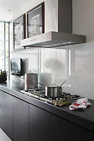 A splashback of clear glass protects the wall behind the hob and the stainless steel chimney extractor is by Gaggenau